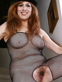 Redheaded grandma in a fishnet body stocking plays with..
