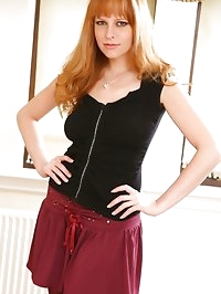 Cute redhead wearing miniskirt, tight top and boots.