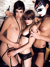 Three fetish masked women in sexy lingerie fucking a cock