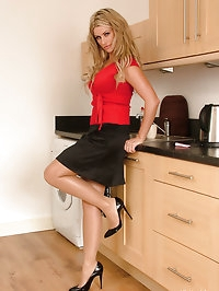 Hot babe Kathryn is teasing in the kitchen in shiny black..
