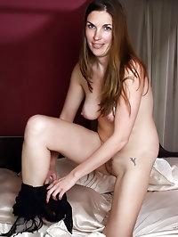 Sexy brunette MILF Phoebe in a black fishnet bodysuit..